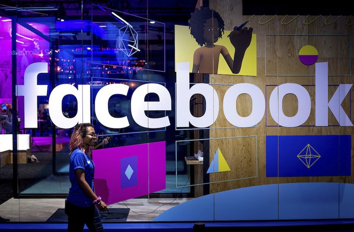 FILE - In this Tuesday, April 18, 2017, file photo, a conference worker passes a demo booth at Facebook's annual F8 developer conference, in San Jose, Calif. Facebook Inc. reports earnings Wednesday, Jan. 31, 2018. (AP Photo/Noah Berger, File)