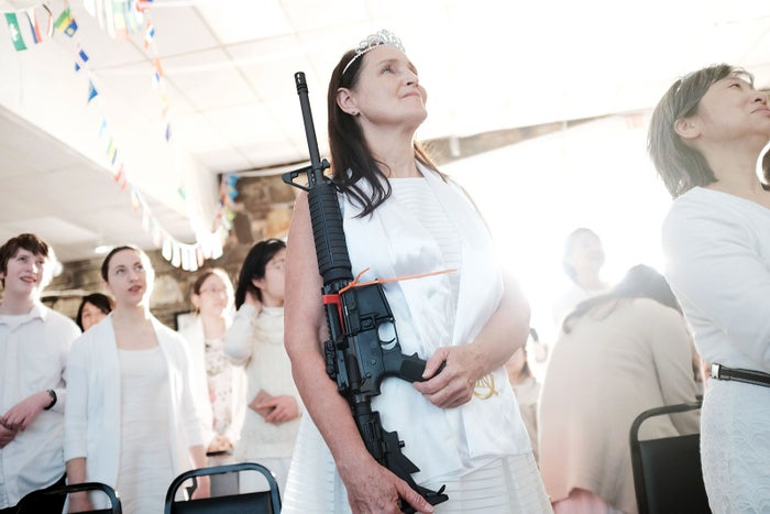 """A woman holds an AR-15 rifle during a ceremony at the World Peace and Unification Sanctuary on Feb. 28, in Newfoundland, Pennsylvania. The controversial church, which is led by the son of the late Rev. Sun Myung Moon, believes the AR-15 symbolizes the """"rod of iron"""" in the biblical book of Revelation."""