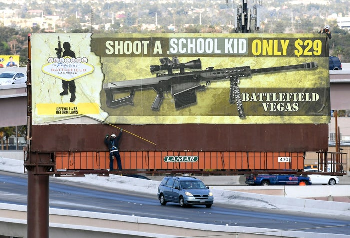 """Workers remove a billboard poster for the Battlefield Vegas shooting range after it was vandalized on March 1, in Las Vegas. An activist art collective took responsibility for putting the words """"SCHOOL KID"""" over the words """".50 CALIBER"""" on the sign. The collective released a statement saying that the protest piece is a response to America's obsession with gun culture and the government's ties with the NRA, and called on politicians to work on reforming gun laws."""