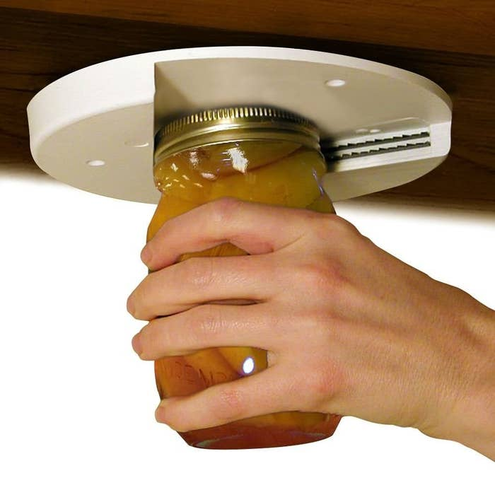 disc-shaped jar opener mounted underneath a cabinet with hand using it to open a mason jar
