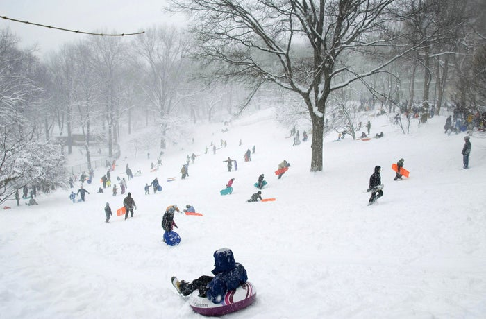 Children and adults go sledding on a hill in Riverside Park on Feb. 12, 2006.