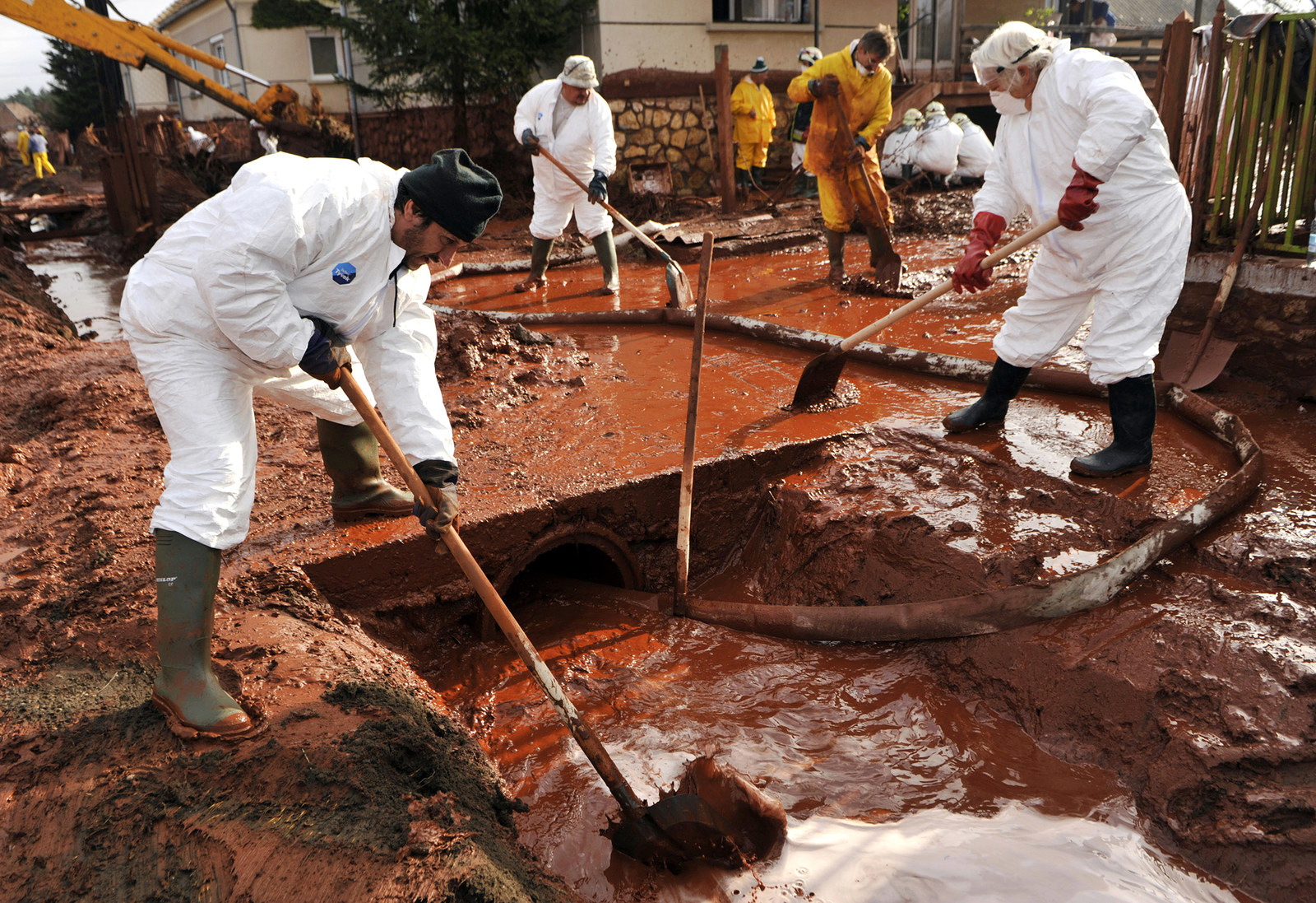 Community workers, wearing protective gear, clean a street flooded by toxic mud in the village of Kolontár, Hungary, on Oct. 7, 2010.