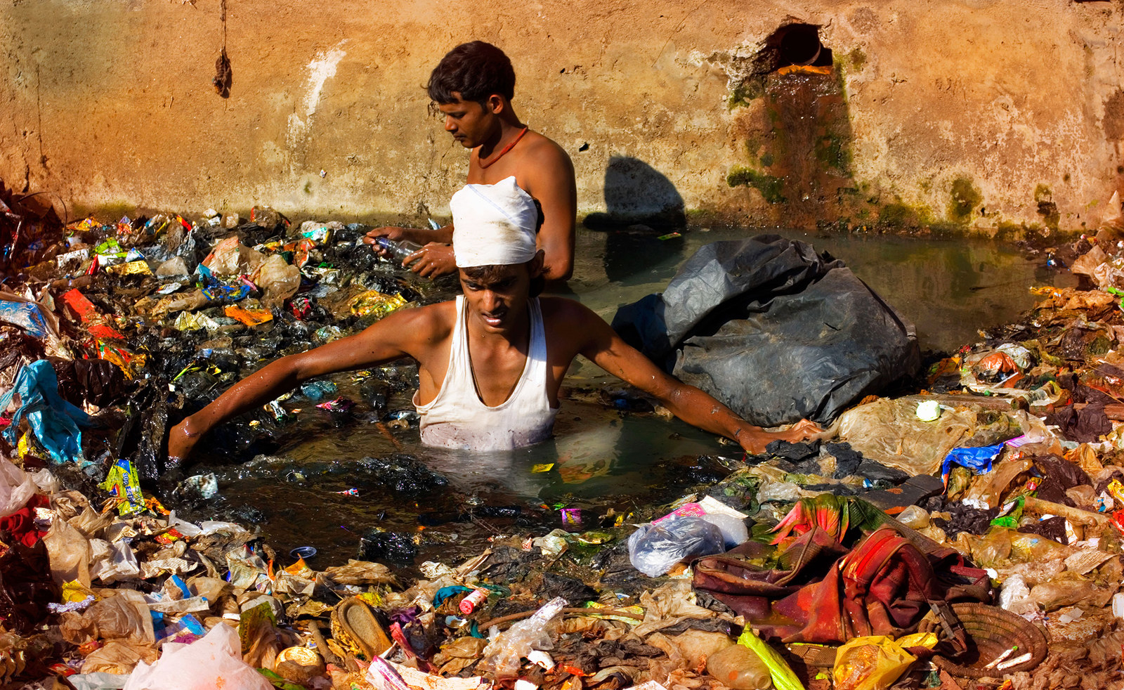 Men scavenge the polluted rivers of Mumbai on Jan. 24, 2013. This particular river is treated like an open drain by the citizens, who discharge raw sewage, industrial waste, and garbage unchecked.