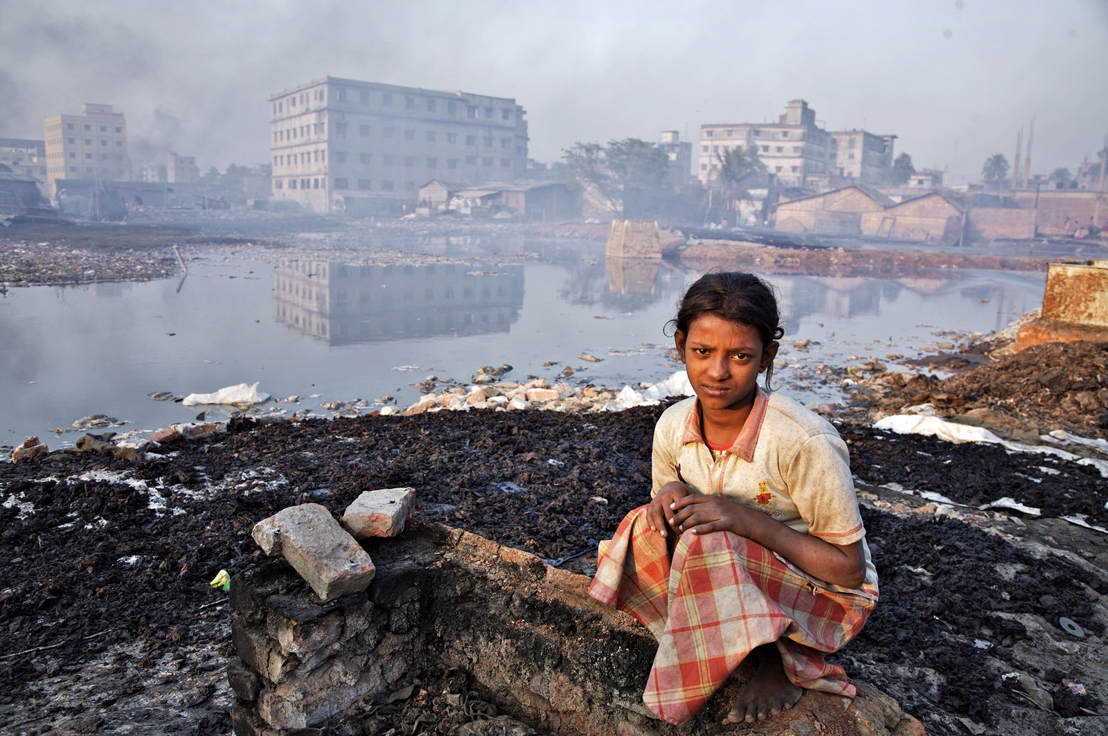 A young girl sits on the broken wall of a glue factory on Feb. 20, 2007, by the side of the Buriganga River in Dhaka, Bangladesh.