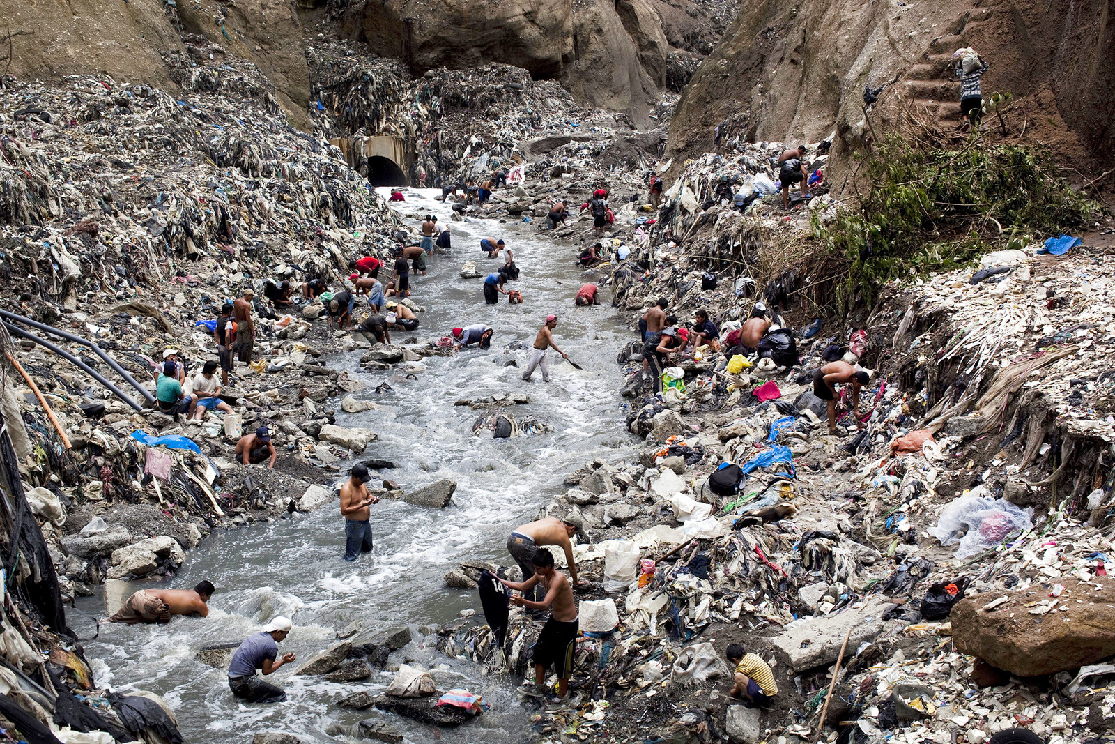 """In this photo taken Oct. 19, 2011, people search for scrap metal in contaminated water at the bottom of one of the biggest trash dumps in Guatemala City, known as """"The Mine."""""""