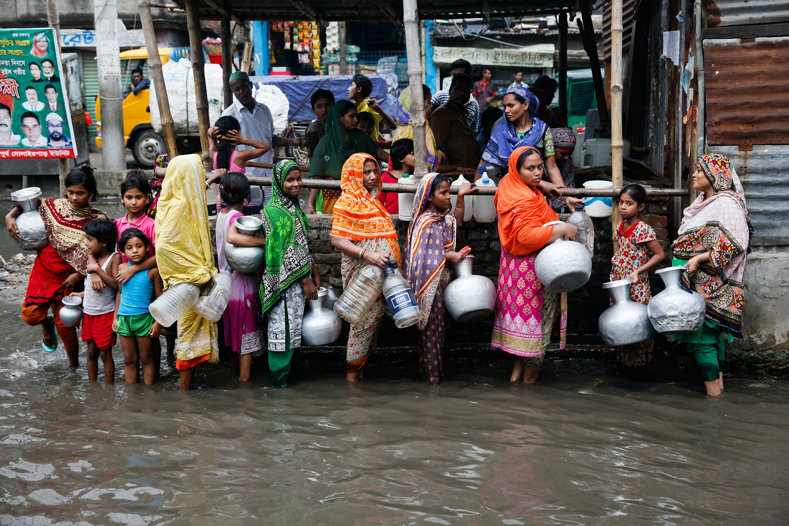 Bangladeshi women and children collect drinking water from a polluted area in Dhaka on June 17, 2017.