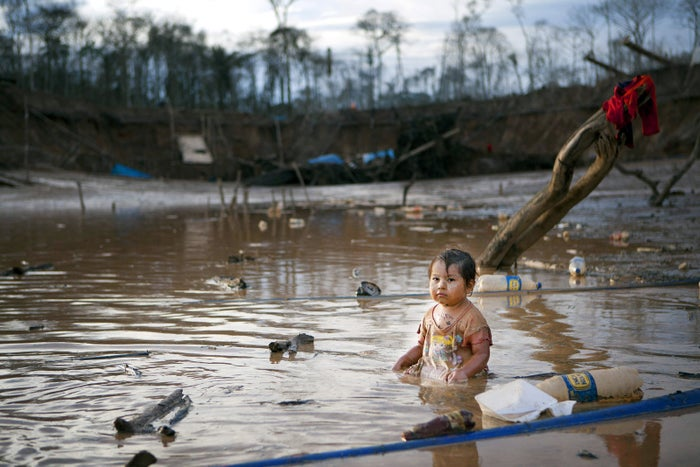 On May 3, 2014, Prisaida, 2, sits in the shallow waters of a polluted lagoon as her parents mine for gold nearby in Peru's Madre de Dios region. The lagoon emerged as a result of miners bombarding the earth with jet streams of water in search of gold.