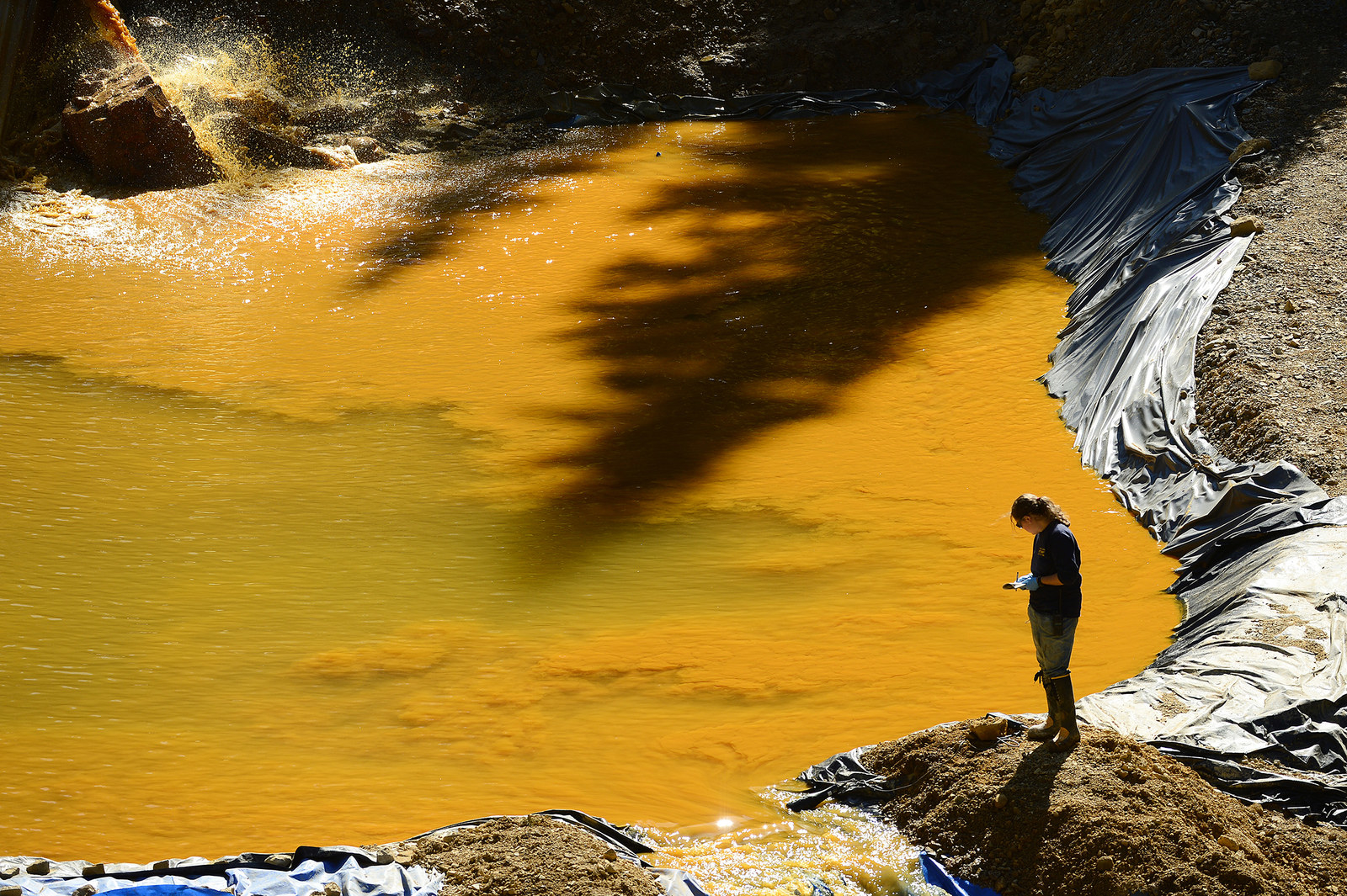 A woman from Weston Solutions walks next to one of the retention ponds at the bottom of Gold King Mine on Aug. 13, 2015, at Gladstone Townsite. Members of the EPA, Environmental Restoration, Weston Solutions, and the US Coast Guard are working on cleaning up the water in the four retention ponds and helping with the creation of the fifth.