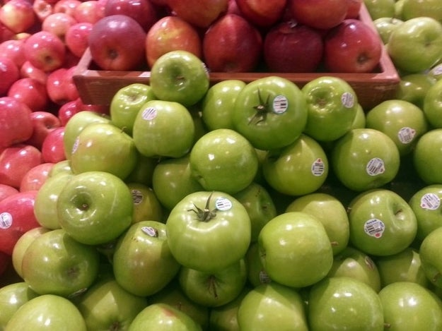 Hide a few green tomatos with the green apples at a grocery store.