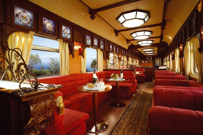 The railcar restaurant in the Golden Eagle's Trans-Siberian Express is clad in red velvet and wooden accents.