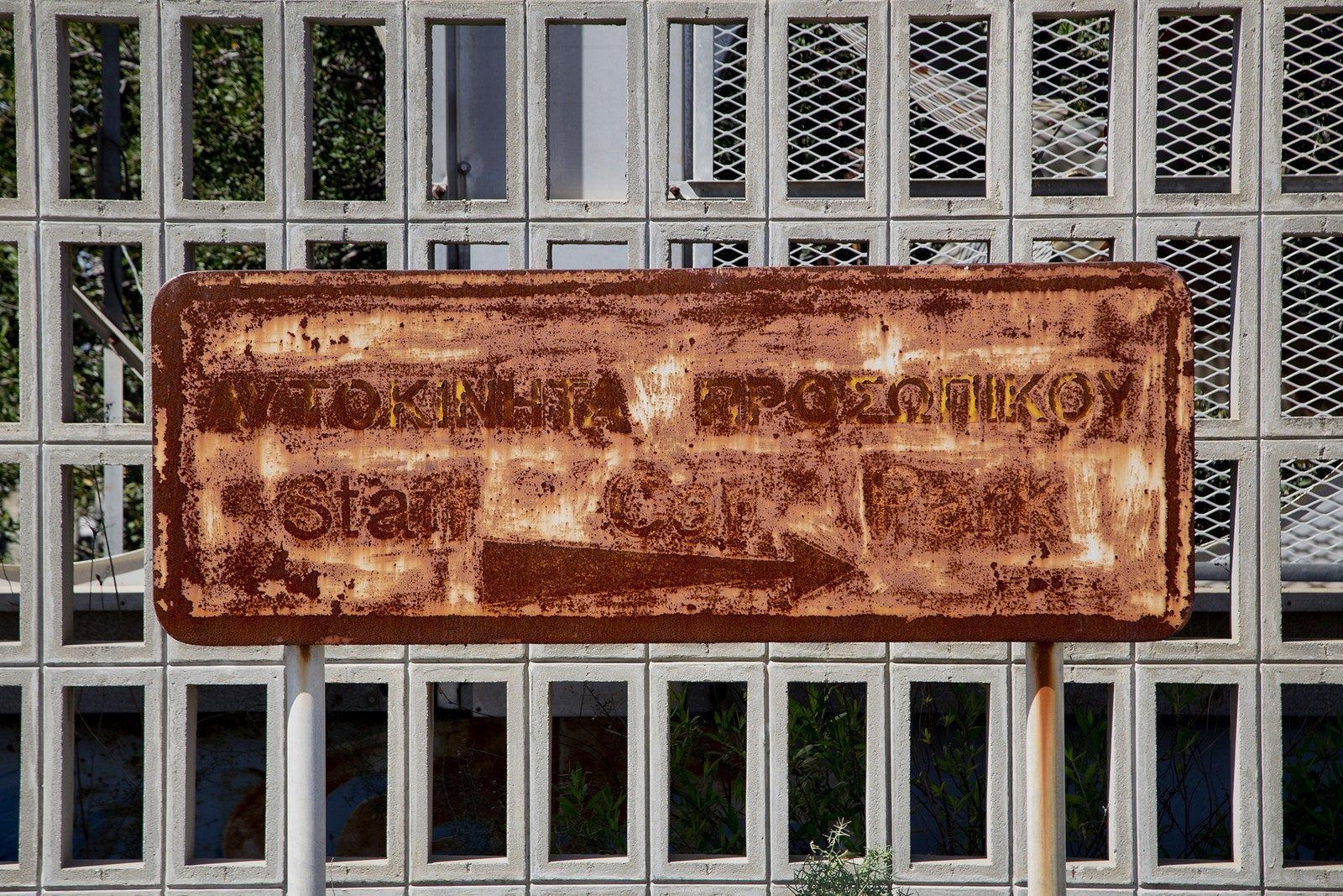 """A sign reading """"staff car park"""" is faded and covered with rust."""