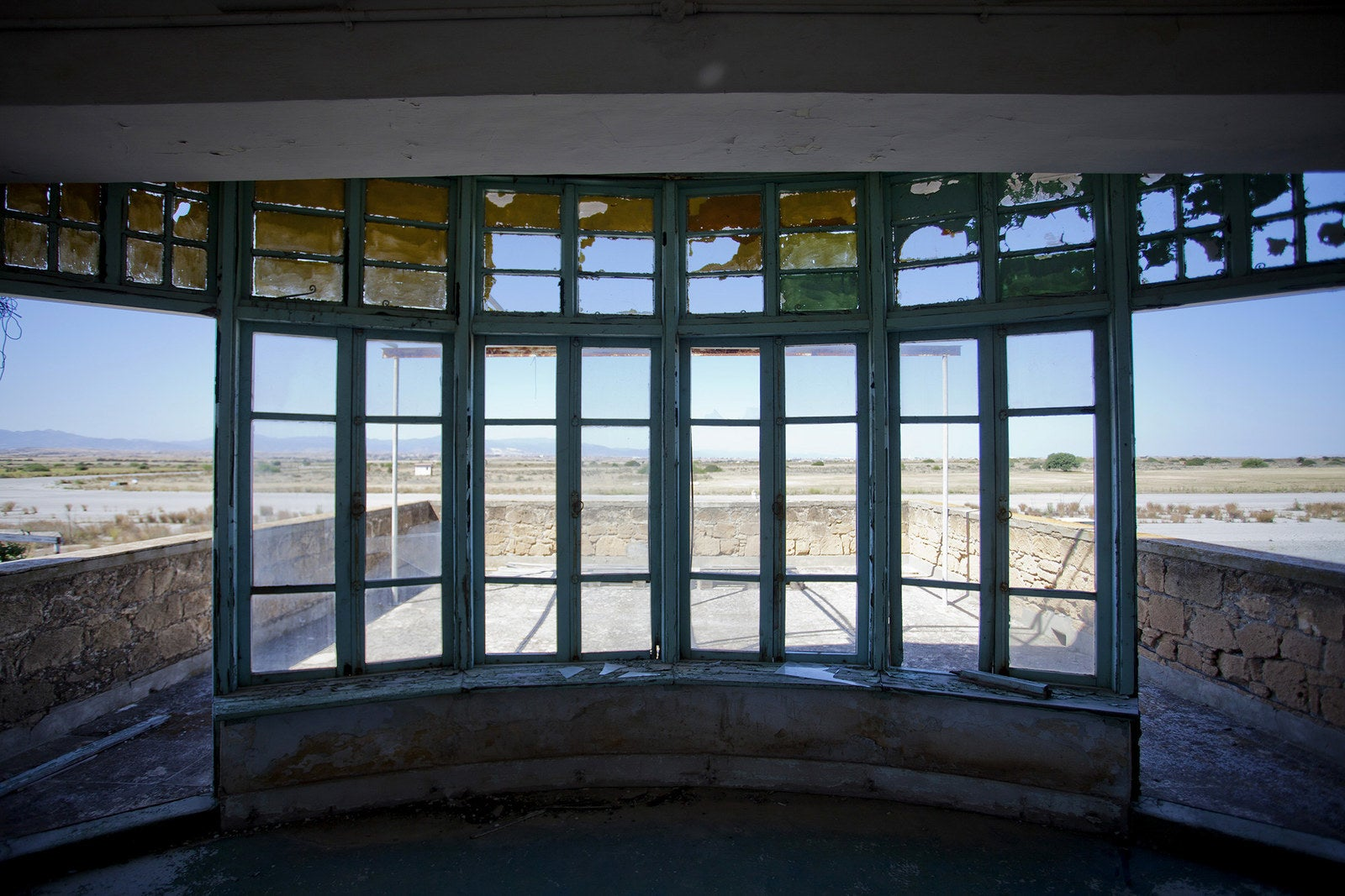 A view from the broken windows of a control tower for the runway.