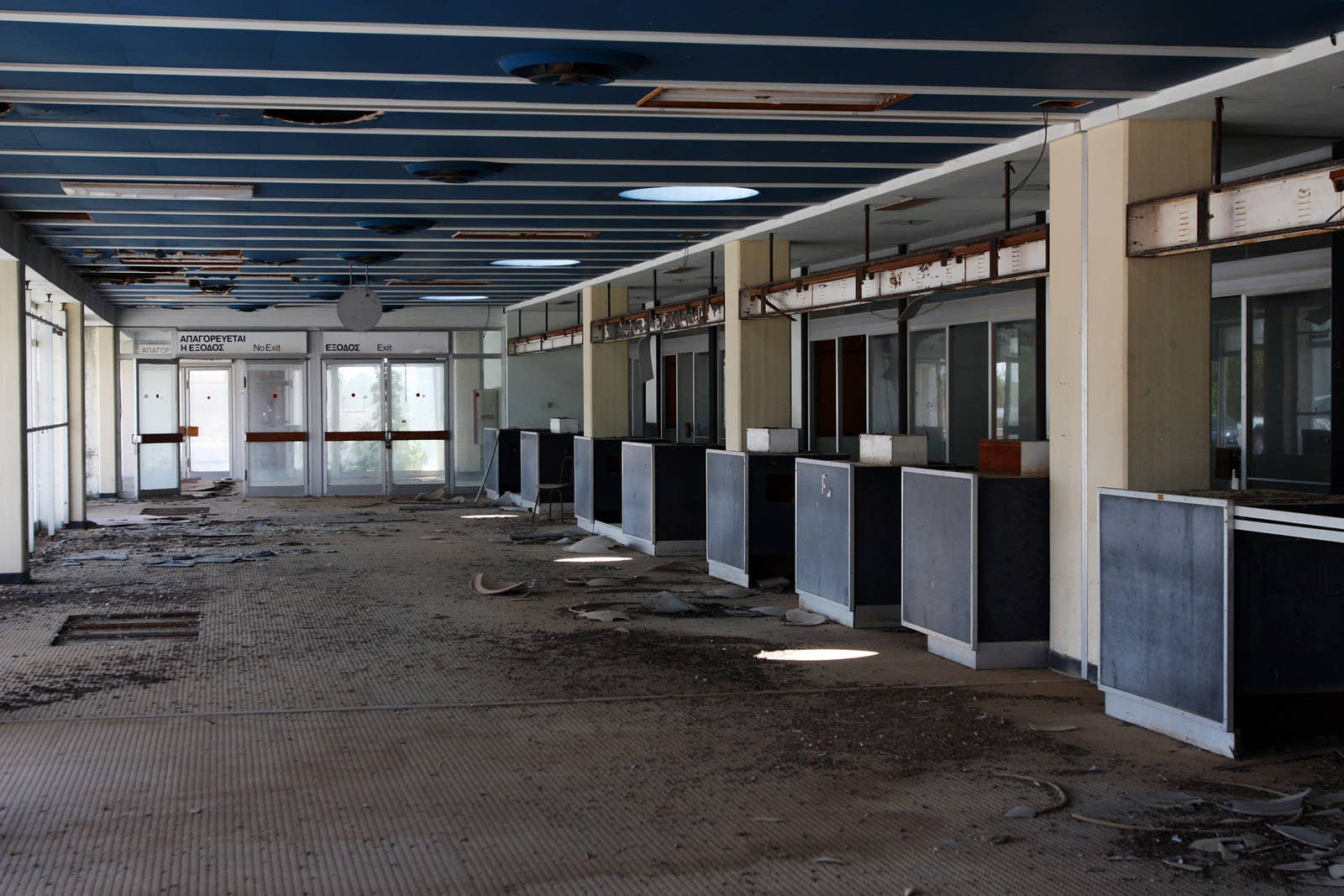 Abandoned ticket counters decay inside the terminal building.