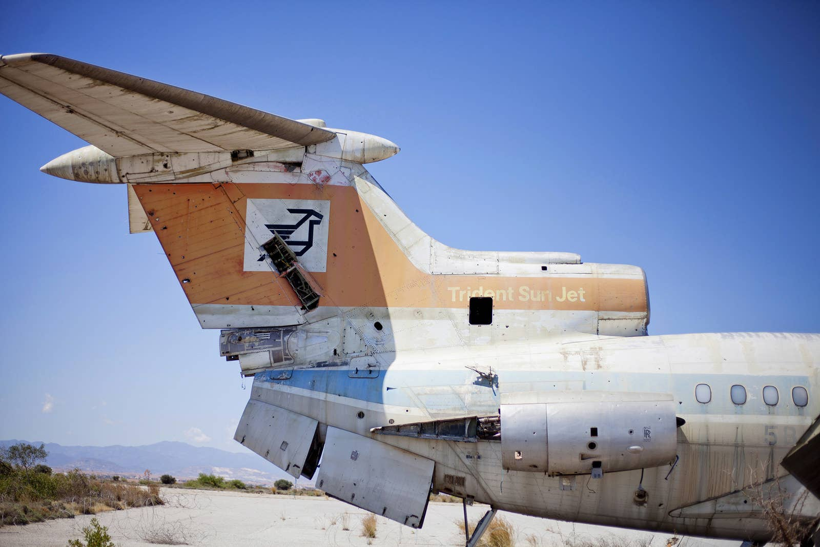The shell of an airplane sits on the runway, slowly rusting.