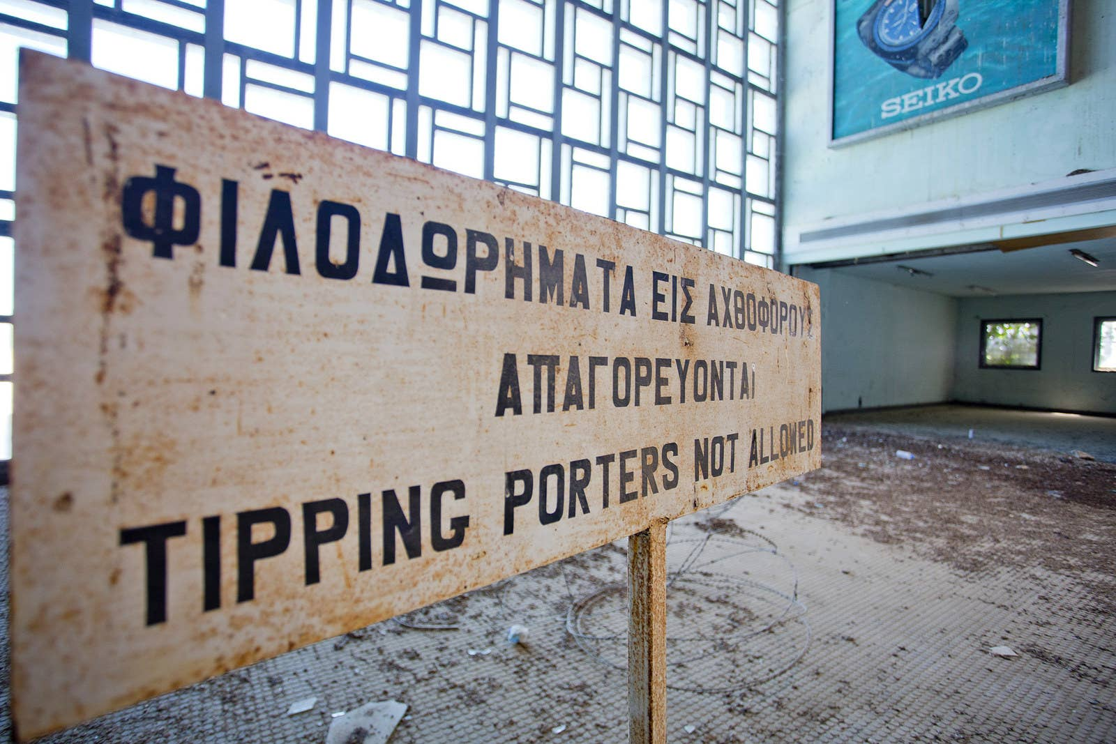 "A sign reading ""tipping porters not allowed"" is left faded with rust."