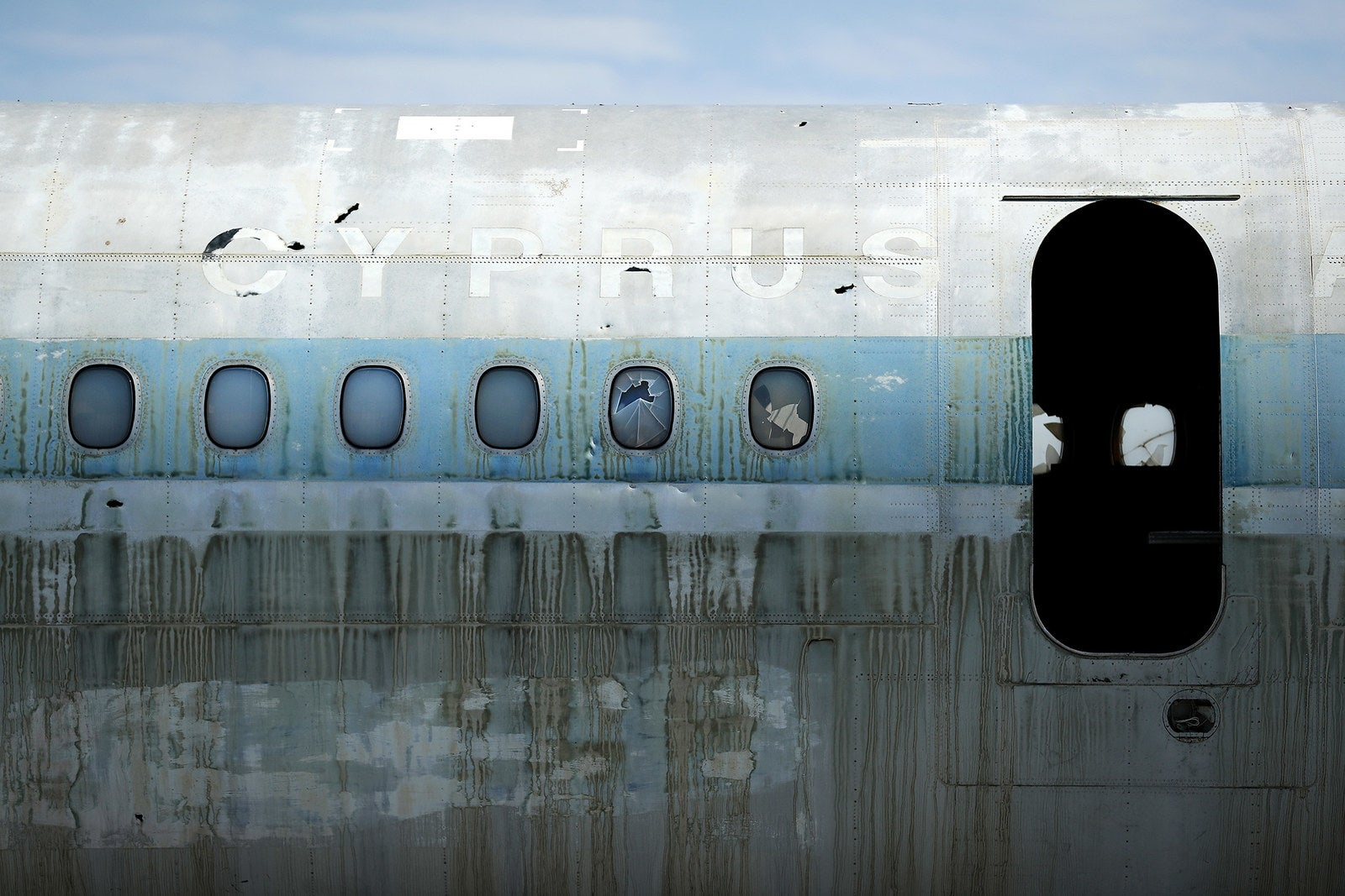 A abandoned and decaying Cyprus Airways passenger plane sits on the runway.