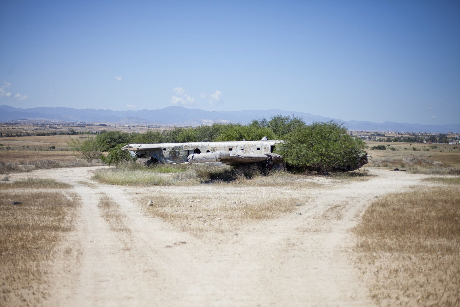 Remains of an Avro Shackleton aircraft is reclaimed by brush and wilderness.
