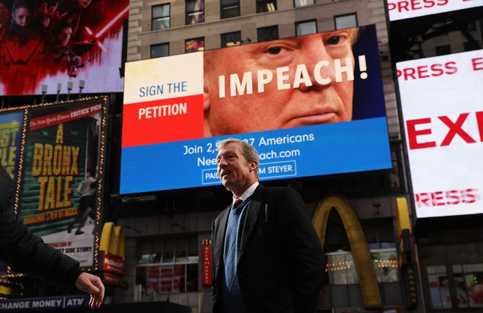 Tom Steyer in front of one of the billboards he has funded in Times Square calling for President Donald Trump's impeachment, Nov. 20, 2017.