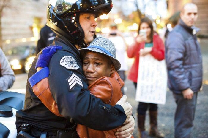 Portland Sgt. Bret Barnum and Devonte Hart, 12, hug at a rally in Portland in 2014.