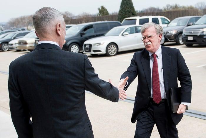 Jim Mattis greets John Bolton.