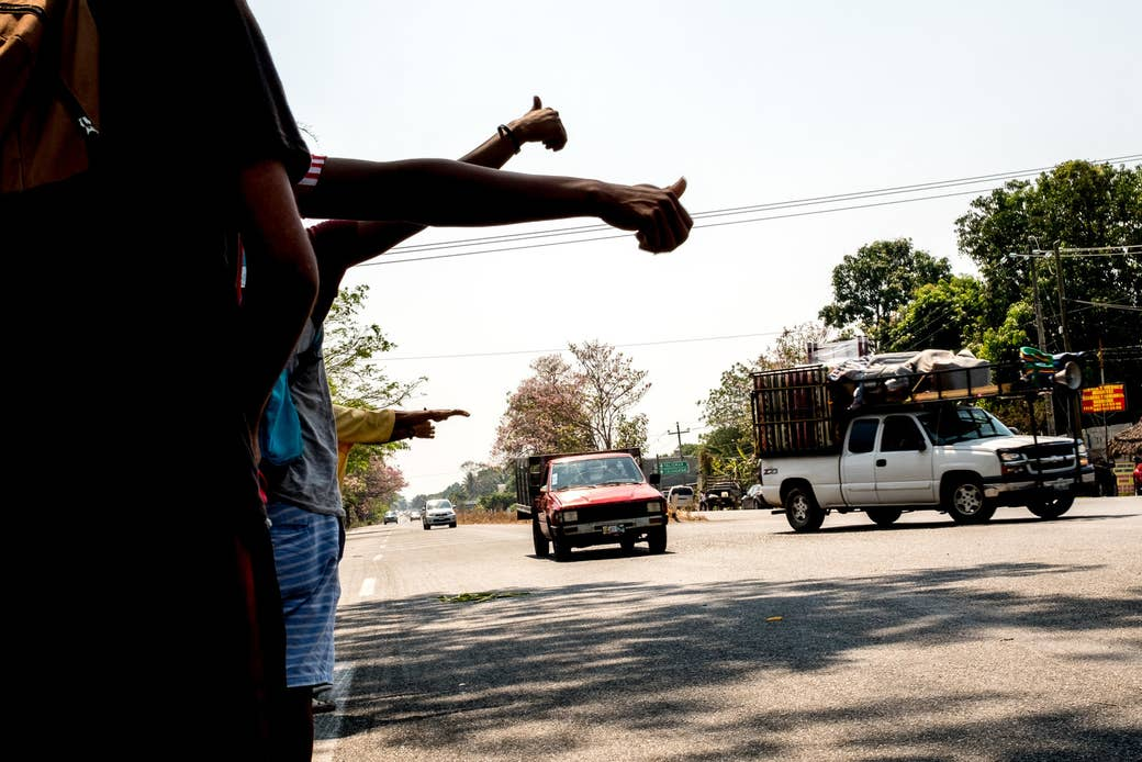 Migrants hitchhike along the side of the highway as they move toward the city of Mapastepec, Chiapas.