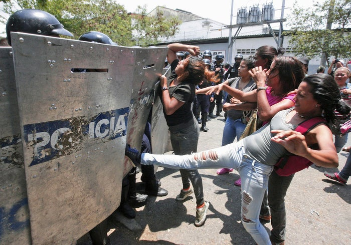 Relatives of prisoners fight with police officers as they wait for information outside a police station in Valencia, Venezuela, on Wednesday.