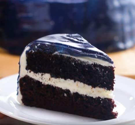 ZUBEREITUNG1. Backe die Kuchen nach Packungsanleitung oder verwende dein Lieblingsrezept.2. Vermische für die Buttercreme Butter, Vanille, Milch und Puderzucker in einer Schüssel mit einem Handrührgerät.4. Wenn die Kuchen gebacken und abgekühlt sind, platziere einen davon auf einem Tortenständer. Wenn du keinen hast, geht auch eine Tortenplatte. Schneide den oberen Teil der Kuchen ab, um eine ebene Fläche zu erhalten.5. Gib einen großen Schlag Buttercreme auf den Kuchen und verteile sie so, dass eine ebenmäßige Glasur entsteht.6. Platziere den zweiten Kuchen auf der Lage Buttercreme.7. Glasiere den kompletten Kuchen, sodass eine glatte Oberfläche entsteht.8. Stelle den Kuchen in den Kühlschrank, damit er kalt bleibt.9. Lass für die Glasur Wasser, Zucker und Kondensmilch in einem Topf eine Minute lang kochen, dann nimm ihn vom Herd.10. Weiche die Gelatine für 5 Minuten in 2 Liter kaltem Wasser ein, presse dann überschüssiges Wasser heraus und mische die Gelatineblätter unter die Zuckermischung.11. Gieße die Zuckermischung über die Schokolade und warte 2-3 Minuten, bis die Schokolade weich geworden ist.12. Vermische mit einem Pürierstab vorsichtig die Schokolade mit der Flüssigkeit. Achte dabei darauf, dass keine Luftblasen dadurch entstehen, dass du den Pürierstab zu hoch hältst.13. Gieße die Glasur durch ein Sieb in eine große Schüssel, damit alle verbleibenden Luftblasen verschwinden.14. Verteile die Glasur auf fünf Schüsseln (eine mittelgroße und vier kleinere).15. Färbe die größte Schüssel mit schwarzer und dunkelblauer Lebensmittelfarbe und rühr gut um, bis die Farbe gleichmäßig in der Glasur verteilt ist.16. Gib in die nächste Schüssel die dunkelblaue Speisefarbe und rühre gut um.17. Gib in die nächste Schüssel die hellblaue Speisefarbe und rühre gut um.18. Gib in die nächste Schüssel die lila Speisefarbe und rühre gut um.19. Gib in die nächste Schüssel die pinke Speisefarbe und rühre gut um.20. Wenn du bereit bist, die Glasur zu benutzen, achte darauf, dass si
