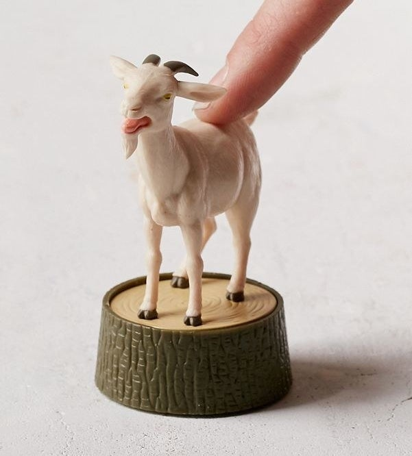 small goat figure with button on back on stump