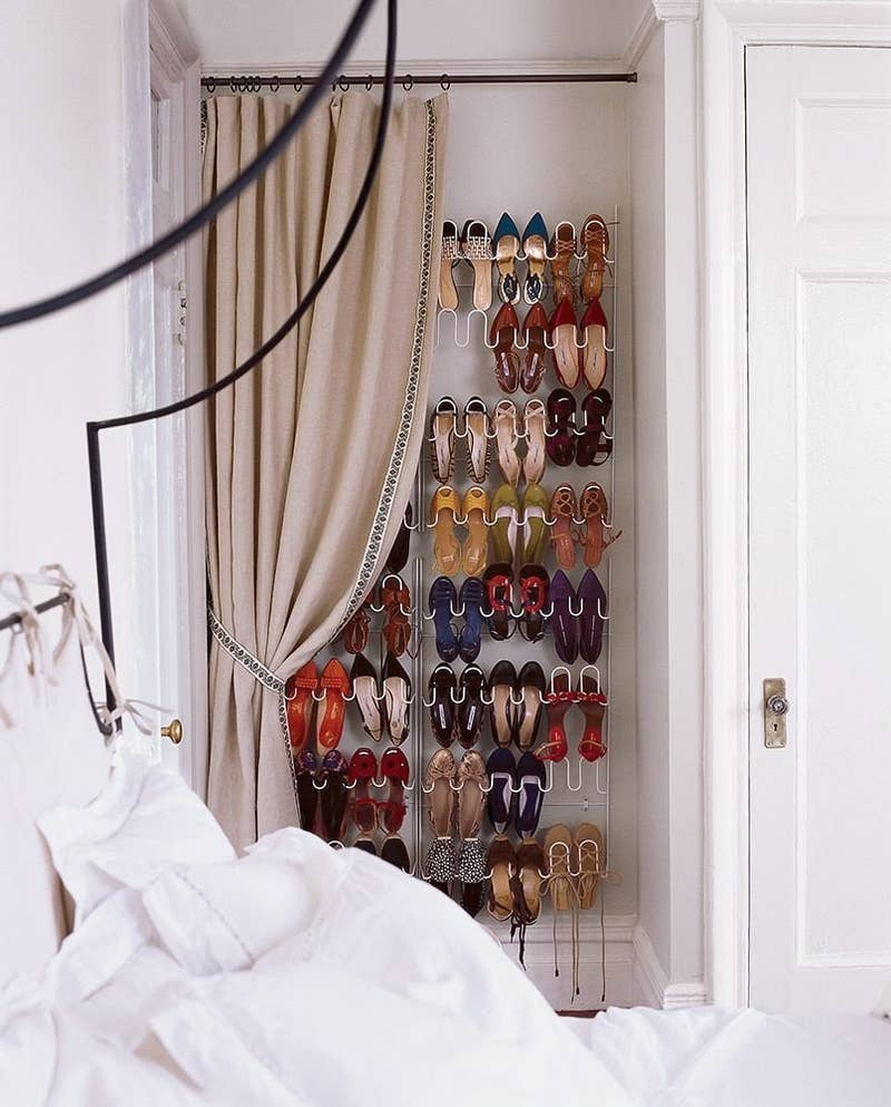 Place a shoe rack against a wall close to your bed and dress it up with an elegant curtain. This way, it will seem like a window or a door, and no one will have to see them.