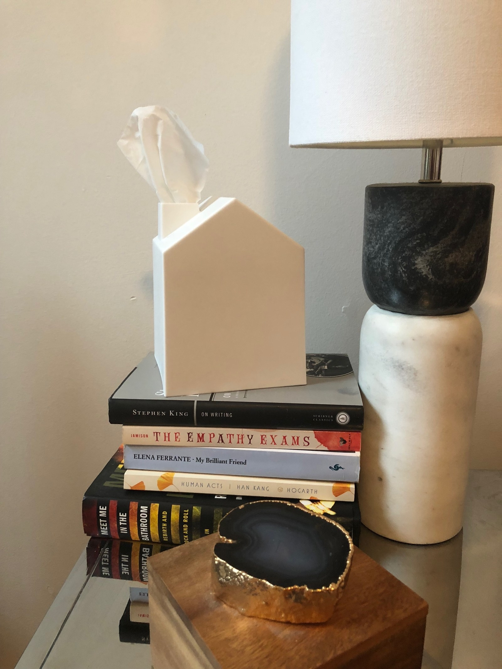 The tissue box covers sitting on a stack of books