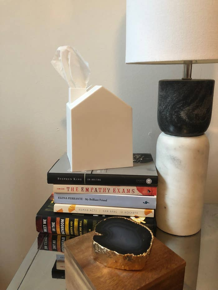 night stand table with a stack of books, lamp, then a square shape house-like white tissue box cover