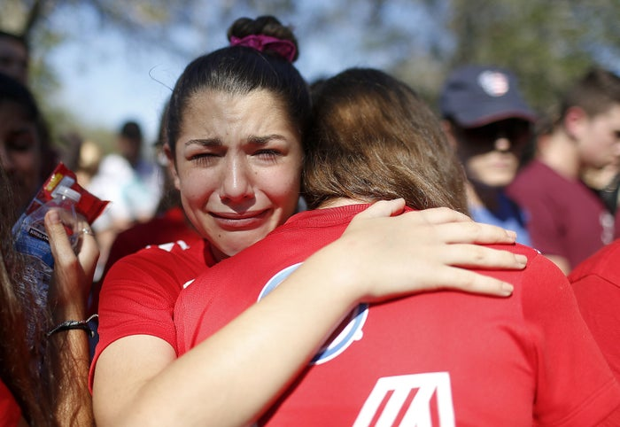 A student mourns the loss of her friend during a community vigil in Parkland.
