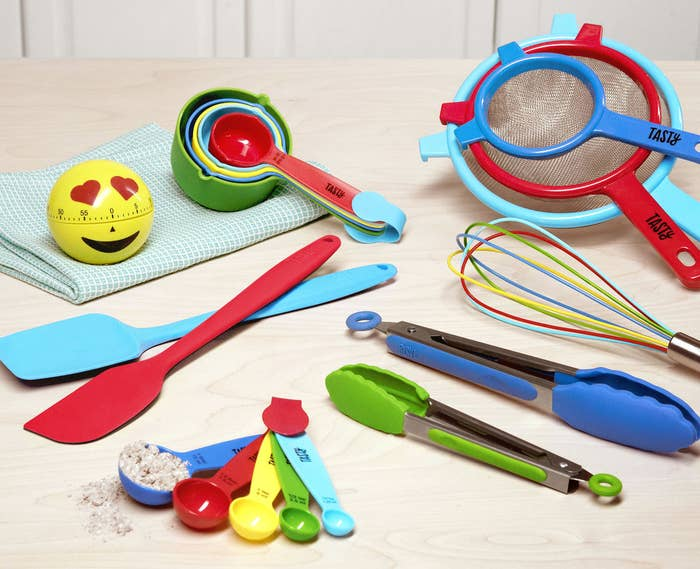 """Set includes an emoji timer, 10-piece measuring spoon and cup set, two-piece 12"""" silicone spatula set, whisk, two-piece tongs set, and three-piece strainer set.Get them from the Tasty collection at Walmart for $33.45."""