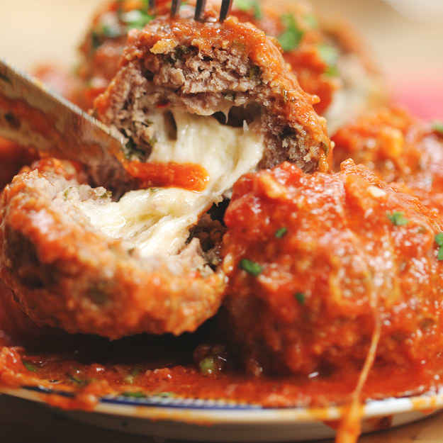 4 servingsINGREDIENTSSauce1.4 kg (7 cups) crushed tomato50 g (1/3 cup) onion, chopped2 cloves garlic, crushed2 teaspoons dried basil1 teaspoon dried oregano1/2 teaspoon pepper1/2 teaspoon saltMeatballs455 g (1 lb) beef455 g (1 lb) mild sausage115 g (1 cup) breadcrumb50 g (1/3 cup) onion, chopped25 g (1/4 cup) parmesan cheese1 teaspoon onion powder1 teaspoon garlic powder1 teaspoon dried thyme1 teaspoon dried oregano1/2 teaspoon salt1/2 teaspoon pepper2  egg4 sticks mozzarella cheese, cut into 4-5 even pieces eachPREPARATION1. Combine all sauce ingredients in slow cooker and stir. Set to high and cover while making meatballs, or for 30 minutes. (Or use pre-made/canned sauce.)2. Combine all meatball ingredients except the mozzarella in a large bowl. Using your hands, mix until fully combined.3. Take a golf ball sized piece of the ground beef mixture and place a piece of mozzarella in the middle. Press meat around the piece of cheese, fully enclosing it. Repeat until all meat is used.4. Place meatballs in slow cooker and submerge in sauce.5. Cover and cook on high for 2-2½  hours, or until meat is fully cooked.6. Serve by itself or over pasta.7. Enjoy!