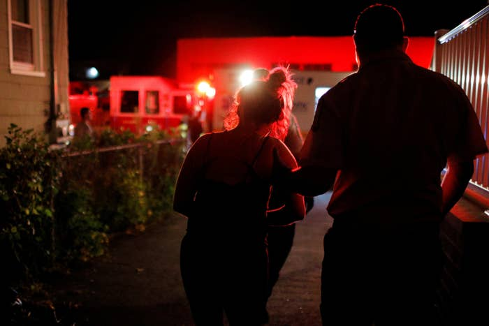 A medic escorts a woman after she was revived from an opioid overdose.