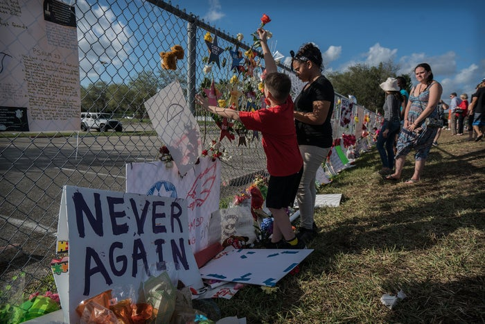 People place flowers, stuffed animals, toys, and signs in a makeshift memorial at Marjory Stoneman Douglas High, where 17 people were killed in a shooting.