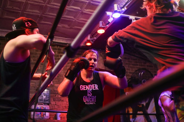 Liv, the collective's trainer, coaches Jessica and another boxer through drills in the ring.