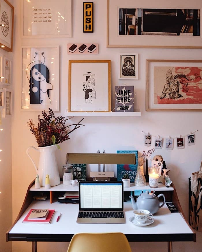 """Living in NYC causes any inch of space to become a Swiss Army Knife of functionality. For a long time I only had my bed or couch as my 'work' area. Acquiring a wall to fit a desk was something I took very seriously. I spent time curating a mini world of inspiration and beauty in which I could create other worlds of inspiration and beauty. Adding fresh flowers, a lit candle, and a pot of tea is a must for me to feel ready to settle into a long writing session."""