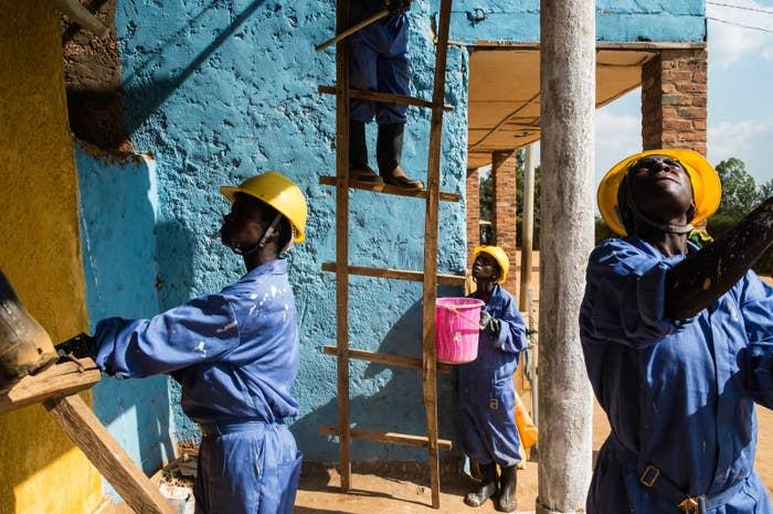Women work on restoring houses in the village Rusheshe for Women for Women International, an NGO.
