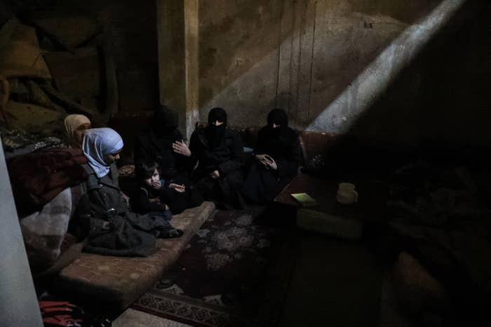 F's family and friends huddle together in the dark below the streets of eastern Ghouta while planes pass overhead. They have been living in their basement since their home was damaged by bombs in late February. They only make quick trips up to the main floor to use the bathroom.