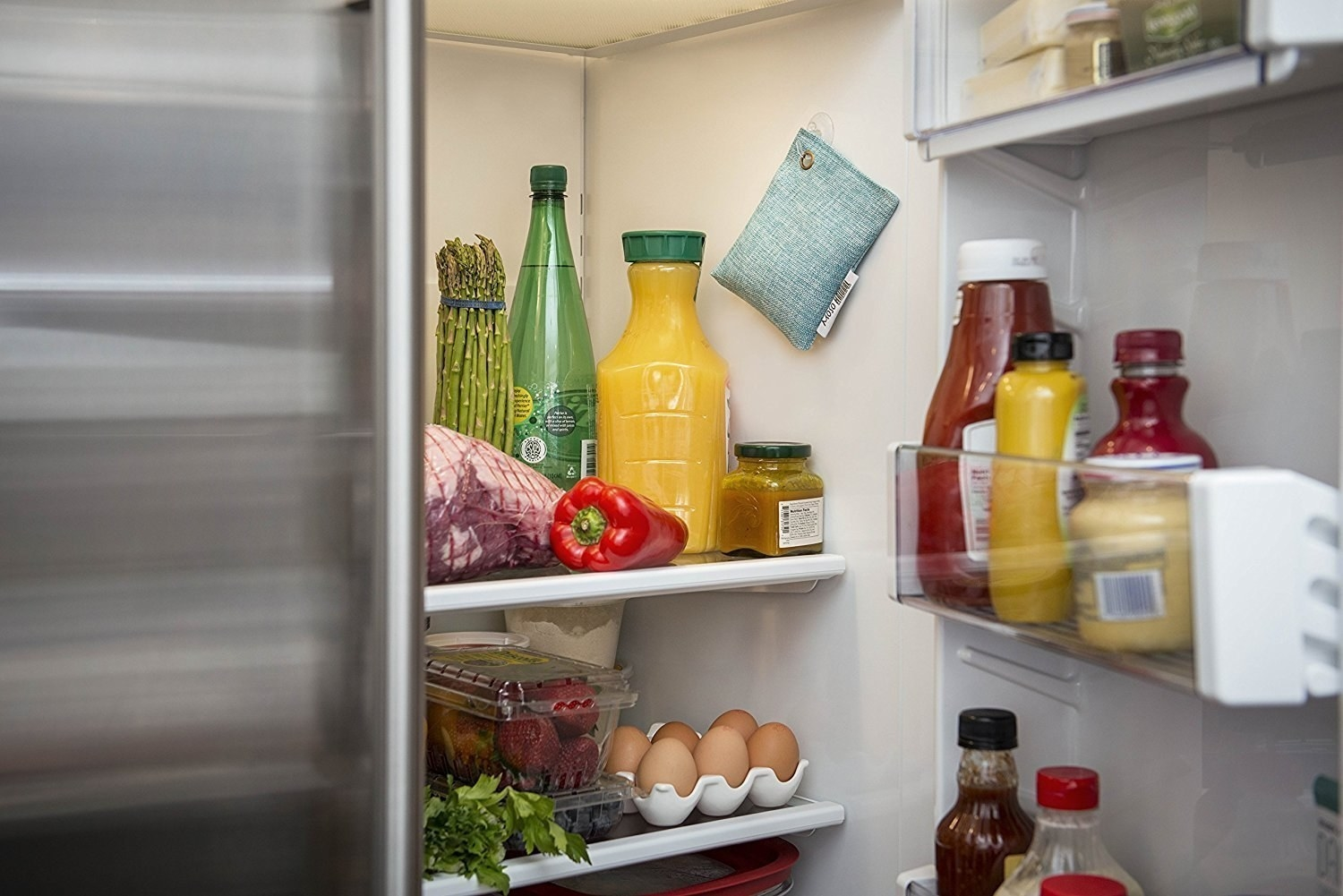 look at the inside of a fridge filled with condiments and produce with a small bag hanging on the inside wall on a stick-on hook