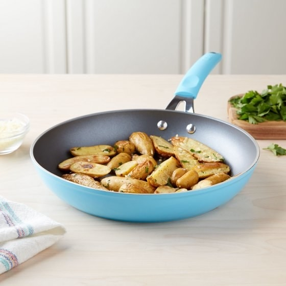 "A bright blue non-stick 11"" frying pan sure to evenly heat everything you could ever want to cook."