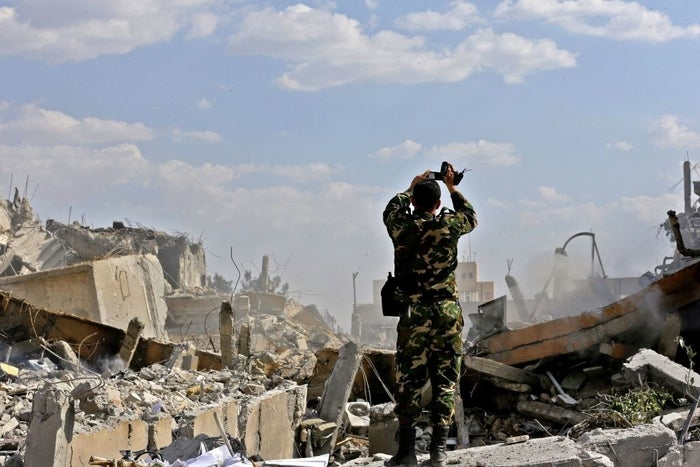 A Syrian soldier inspects the wreckage of a building described as part of the Scientific Studies and Research Centre in the Barzeh district, north of Damascus, during a press tour organised by the Syrian information ministry, on 14 April.