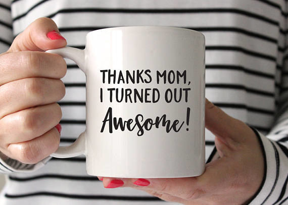 """model holding white mug that reads """"thanks mom, I turned out awesome!"""""""