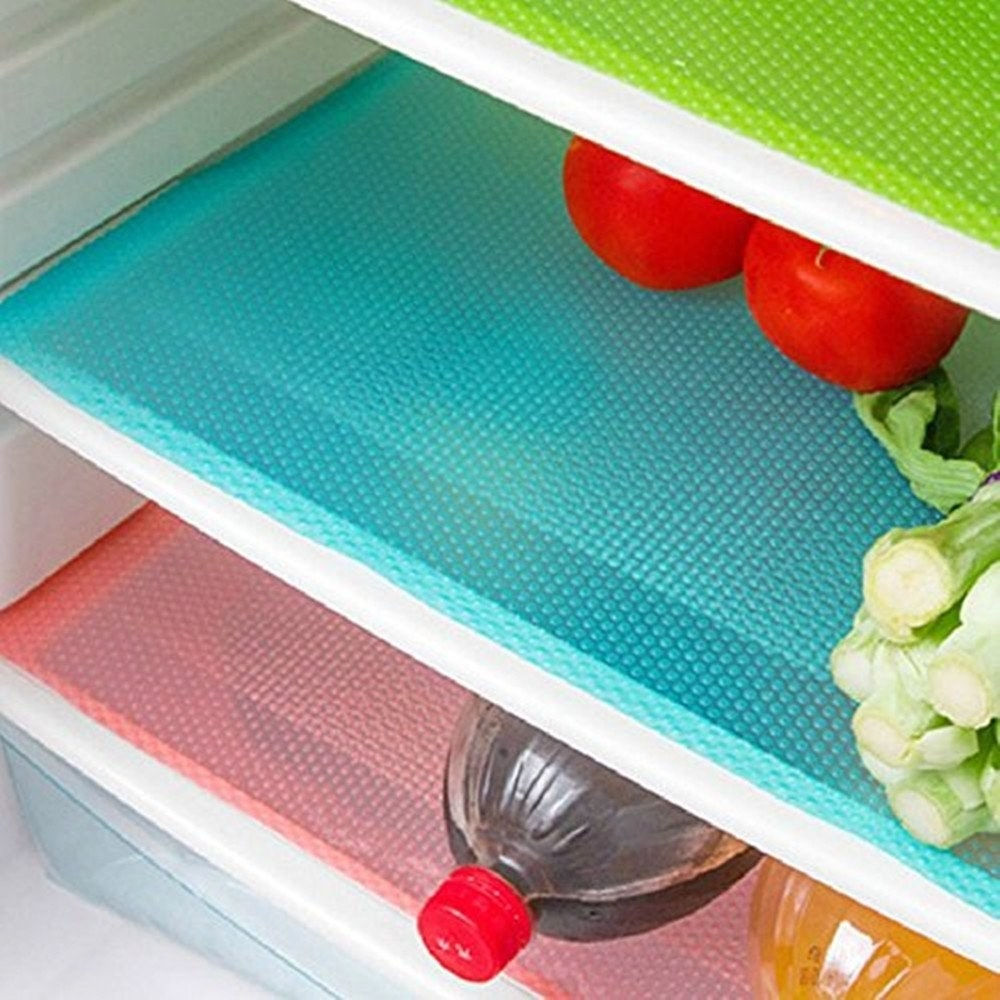 shelves inside a fridge with colorful mats underneath the fridge contents