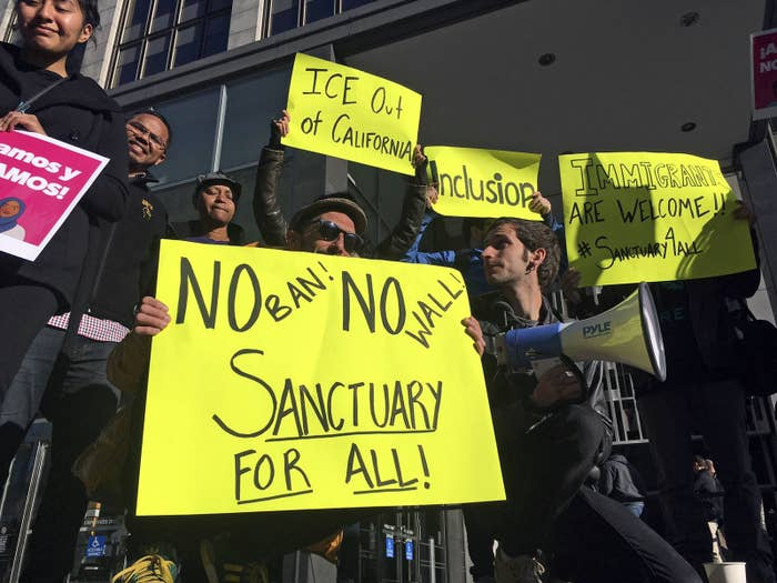 Protesters hold up signs outside a courthouse in San Francisco.