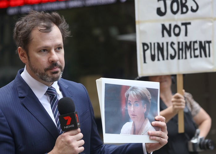 Labor frontbencher Ed Husic holding up a photo of jobs minister Michaelia Cash.