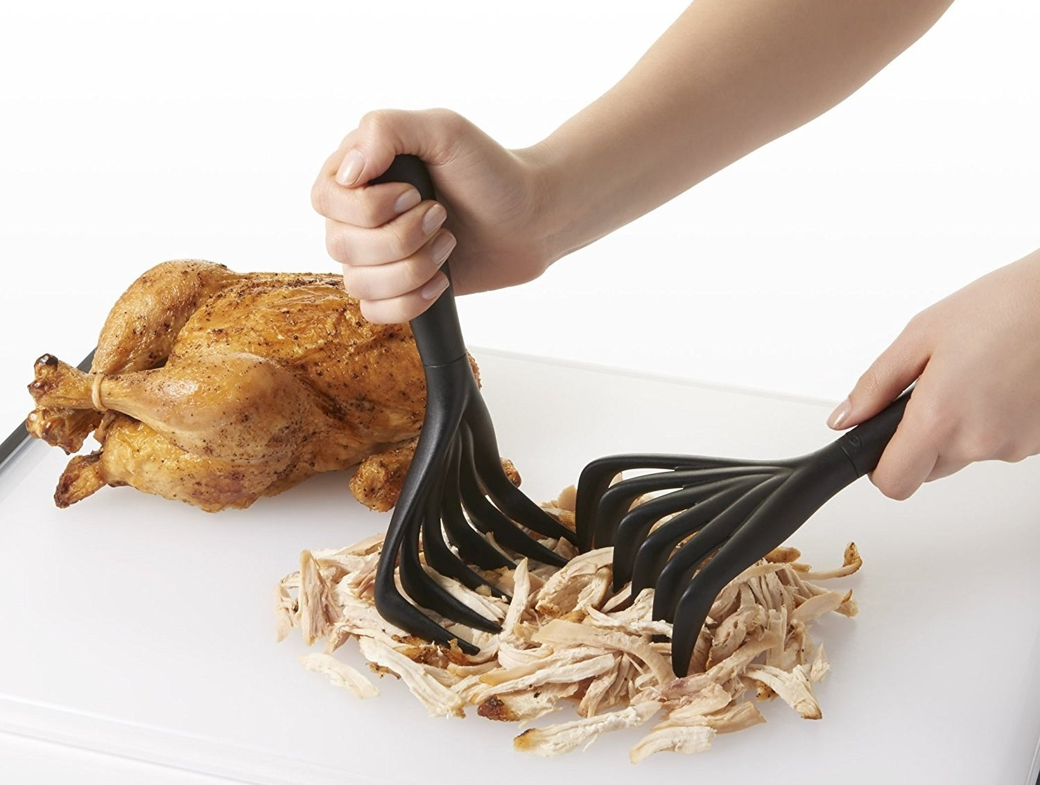 Hands shredding a rotisserie chicken with the black claws