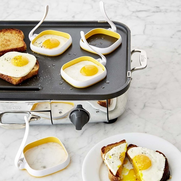 Eggs on a griddle cooking in the square rings so they fit on toast