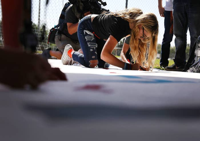 Delany Tarr, a senior at Marjory Stoneman Douglas High School, signs a poster as she gathers together with some of her fellow students after walking out of school in protest.